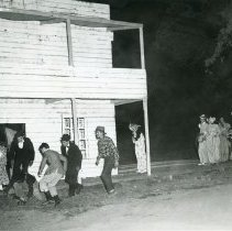 Image of TP2127 - Group-Child hurt, lying on ground in front of a building. Men and woman hurrying to help the child. A group of people standing around watching. Tuolumne Gold Centennial Celebration 1948-50.