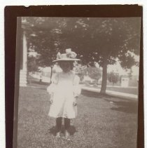 Image of A young girl standing on a lawn.