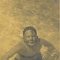 Image of A boy at the Palm Beach Bath and Tennis Club's swimming pool.