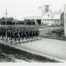 Image of Men in military uniform marching on West Main Road.