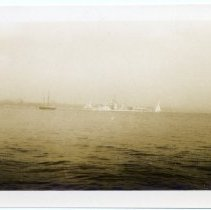 Image of Sailboats and ships near an unidentified coastline.