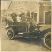 Image of An automobile with passengers outside the Pope Automobile Garage.