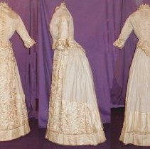 "Image of DRESS, (3 PC.) CREAM COLORED SILK DAMASK SURAH (C NOT YET � LOCATED-11/7/2003) - DRESS, MACHINE & HAND STITCHED. A=BODICE: LINED IN LINEN.  �FITTED, CENTER OPENING WITH LONG, POINTED END ON BACK.  STAND-UP �COLLAR WITH ADDITION OF GATHERED GROSGRAIN RIBBON.  ENDS OF �SLEEVES HAVE BEEN TURNED IN TO CHANGE STYLE & THE GATHERED, �GROSGRAIN RIBBON HAS BEEN ADDED AT THAT TIME. B=SKIRT; A-SHAPED �SKIRT WITH FLAT FRONT & SIDES & GATHERED AT WAIST OVER 'BUSTLE' �AREA.  COTTON WAISTBAND WITH A BUTTON CLOSURE. FRONT HAS PANEL OF� HORIZONTALLY GATHERED SILK, 5 COLUMNS WIDE (AUSTRIAN VALANCE �STYLE). BOTTOM OF SIDES HAS SAME DESIGN 16"" FROM HEM & THERE ARE �5"" HIGH CARTRIDGE PLEATS WITH SILK LINING & TWILL TAPE PIPING �AT HEM.  LARGE AREA OF SKIRT BACK IS MADE OF LINEN (THE PANEL �MEANT TO GO OVER THIS SECTION IS CURRENTLY MISSING.)"