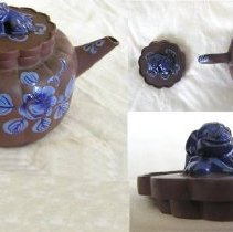 Image of TEAPOT & COVER (CLOSEUP OF SEPARATE PIECES & FINIAL IN IMAGE) - SQUAT, YIXING CHINESE EXPORT RED GLAZED STONEWARE TEAPOT WITH �LID.  NUMEROUS LOBES AT TOP OF BODY, OPENING OF POT & OUTER SHAPE� OF COVER.  COBALT & LIGHT BLUE OVERGLAZE ENAMEL FOLIATED �DECORATION ON UNGLAZED BODY.  COBALT BLUE FOO DOG FINIAL ON �COVER.  (CHINESE CHARACTERS ON INSIDE OF LID & BOTTOM OF POT).  �PULLED HANDLE & SPOUT.