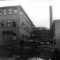 Image of PHOTOGRAPH, WITHUM'S SHOE FACTORY, RUSSELL ST. - BLACK & WHITE PHOTOGRAPH OF THE SHOE FACTORY SHOWS THE BUILDING �IN A STATE OF DISREPAIR WITH BROKEN WINDOWS & PILES OF BOARDS �SCATTERED ABOUT.