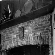 Image of PHOTOGRAPH, FIREPLACE, USED AT THE PEACOCK TEA ROOM, COR. OF �DARLING & FRONT STS. - SEPIA TONED PHOTOGRAPH, MOUNTED, WOOD FRAME, UNDER GLASS, OF �BRICK FIREPLACE. MANTEL SHELF SHOWS 16TH-17TH CENTURY SAILING SHIP� MODEL, PEWTER PLATES. COOKING IMPLEMENTS IN FIREPLACE, �CANDLESTAND TO RIGHT OF FIREPLACE OPENING. SMALL PORTION OF �WINDSOR CHAIR ALSO VISIBLE, AT RIGHT.  PAINTED (WOOD?) STYLIZED �FEMALE HEAD ATTACHED TO BRICK FACE OF FIREPLACE OVER FIREPLACE �OPENING.