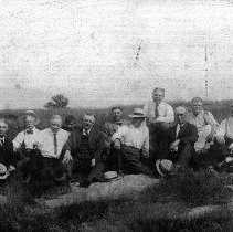 Image of PHOTOGRAPH, 11 MEN SEATED ON A LARGE ROCK OUTCROPPING