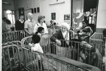Image of Mother Teresa touring a children's ward in a hospital with 3 people.