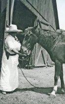 Image of Rhoda A. Rindge (with pistol!) feeding horse