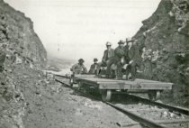 Image of Fred Rindge Jr on railway flat car - RMb-77