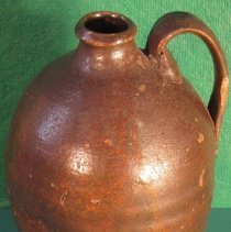 """Image of Jug - Pottery jug, fired red clay jug with handle, 1 quart, small mouth, brown glaze, incised thumb print """"dimple"""" and horizontal lines."""
