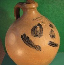 Image of Jug - Pottery, 4 gallon jug, small mouth ovoid beige-gray, salt glaze, three tulips in cobalt blue under glaze opposite handle.  Has a carved wooden stopper.