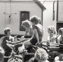 Image of main street, kids on fire truck, 1976