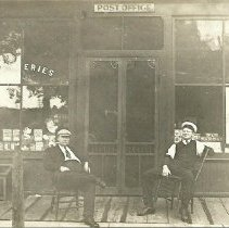 Image of Evergreen Park Post Office and Grocery Store with two unknown individuals, circa 1912. - Print, Photographic