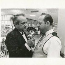 Image of Two unknown individuals talking into a WTAQ microphone, 1958.  - Print, Photographic