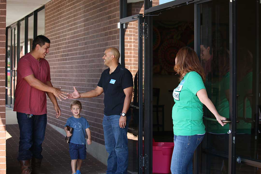 man greeting at front door