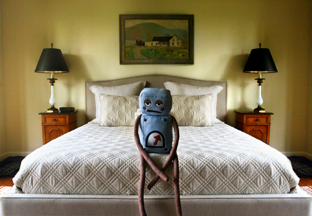 Photo of a blue, sad, plush robot sitting on a bed.