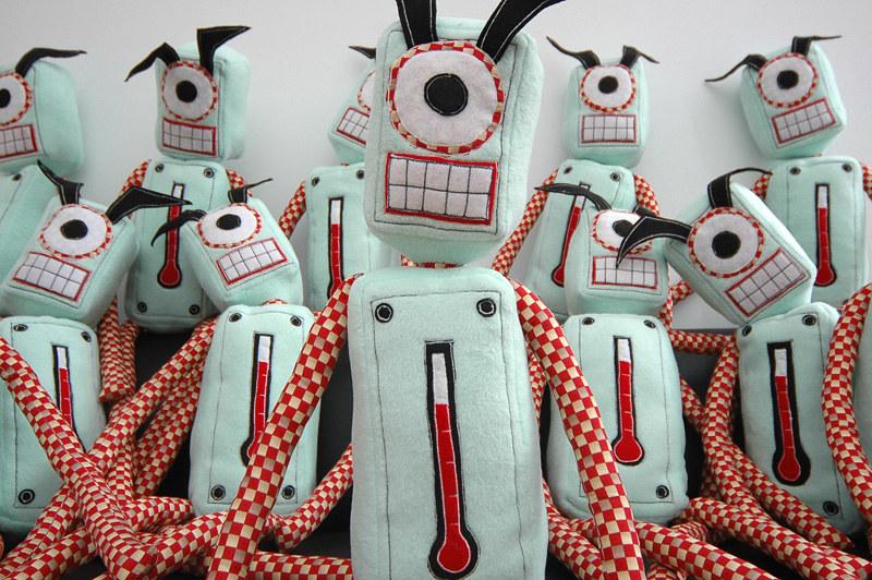 Photo of several green, cycloptic, plush robots.