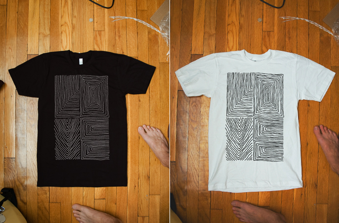Photo of a black shirt with a white line art printed on it and a white shirt with black line art printed on it.