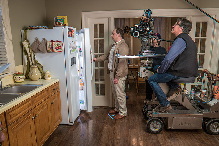 On a dolly, cinematographer Robert Brinkman captures a scene.