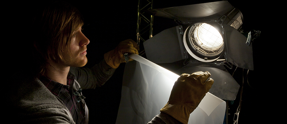 Lighting man placing a sheet of diffuser on a studio light in a Television studio; Shutterstock ID 127288280
