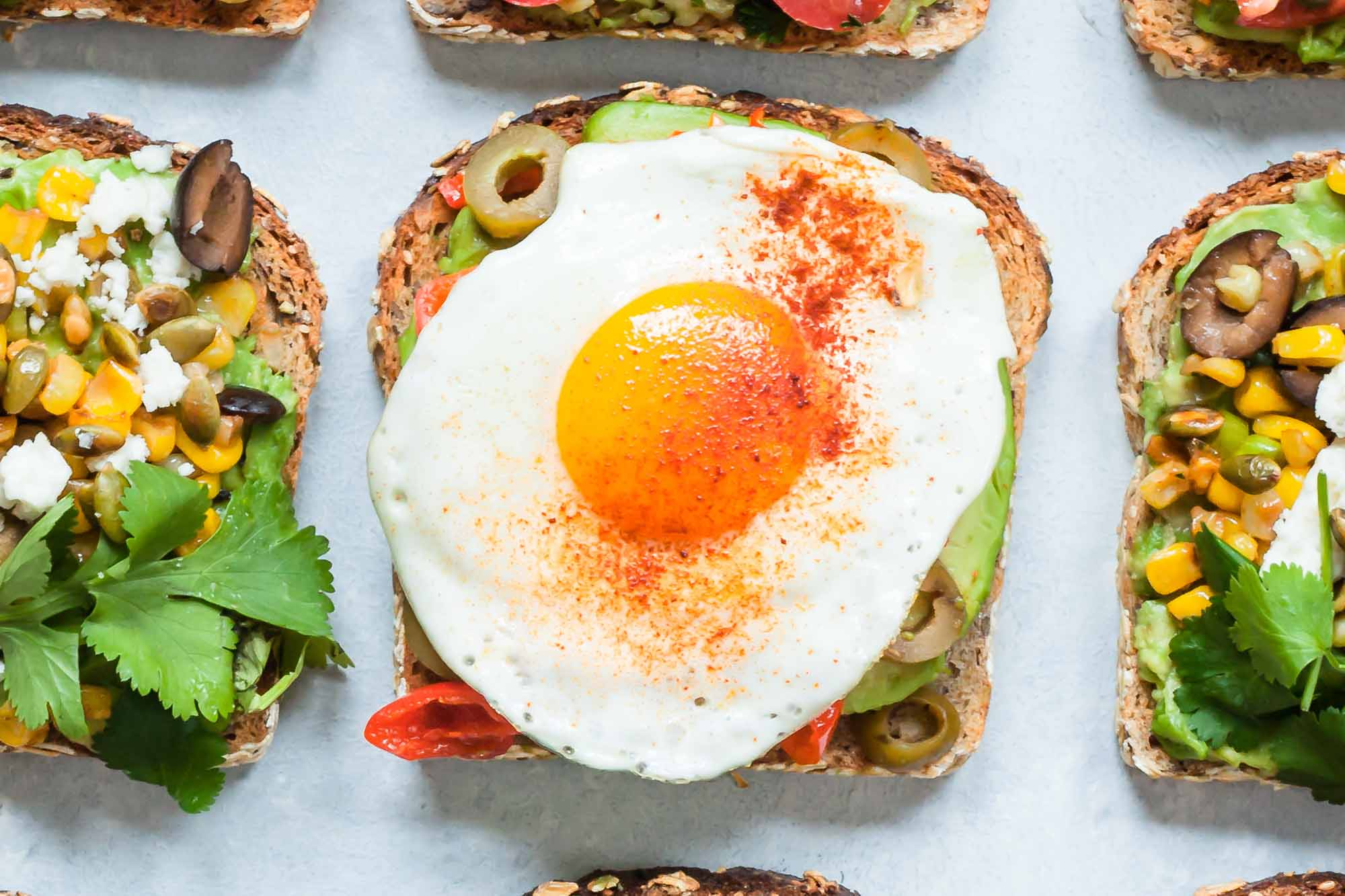 Avocado Toasts with Fried Egg, Olives, and Smoked Paprika