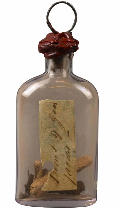 Glass bottle with nail, pin, and bone from the mid-nineteenth century. Object 108406