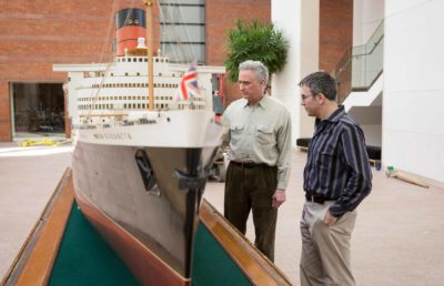 Examining the model of the Queen Elizabeth before it's raised.