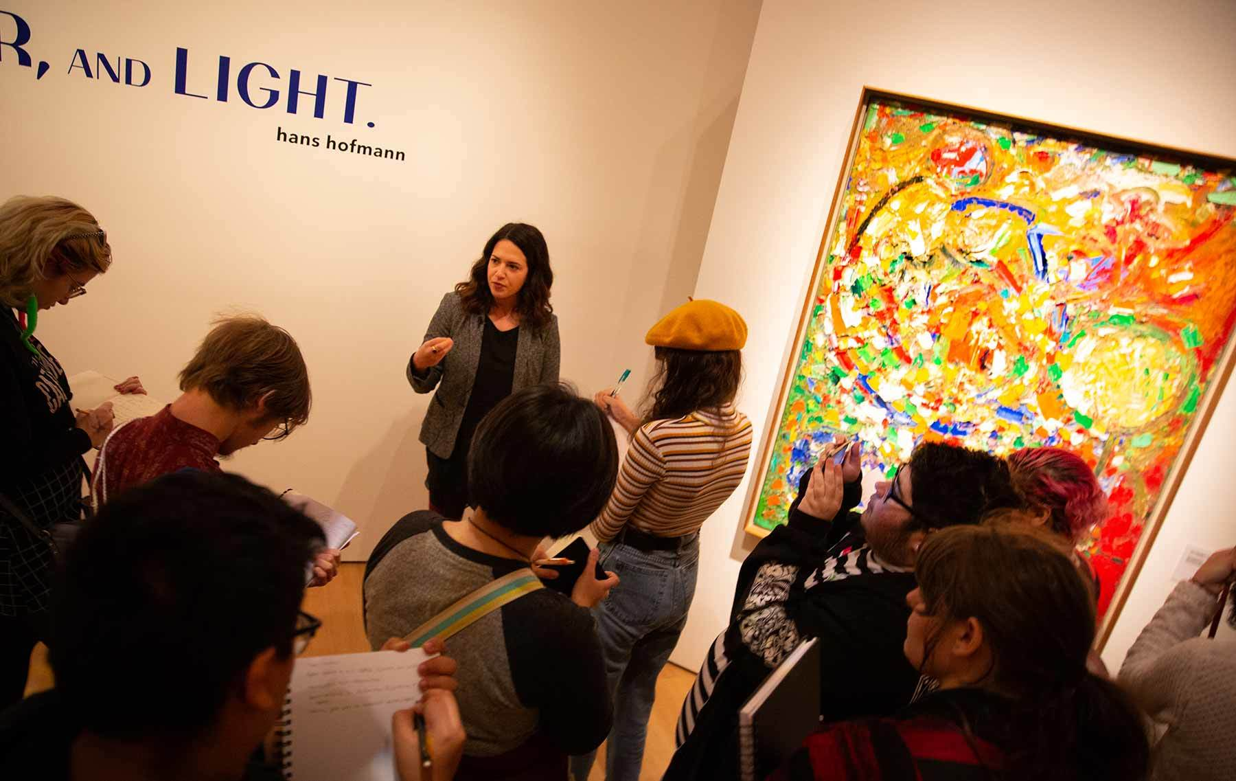 A group of students pause at Hans Hofmann's painting The Garden