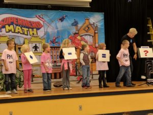 Students solving number sentences on stage.
