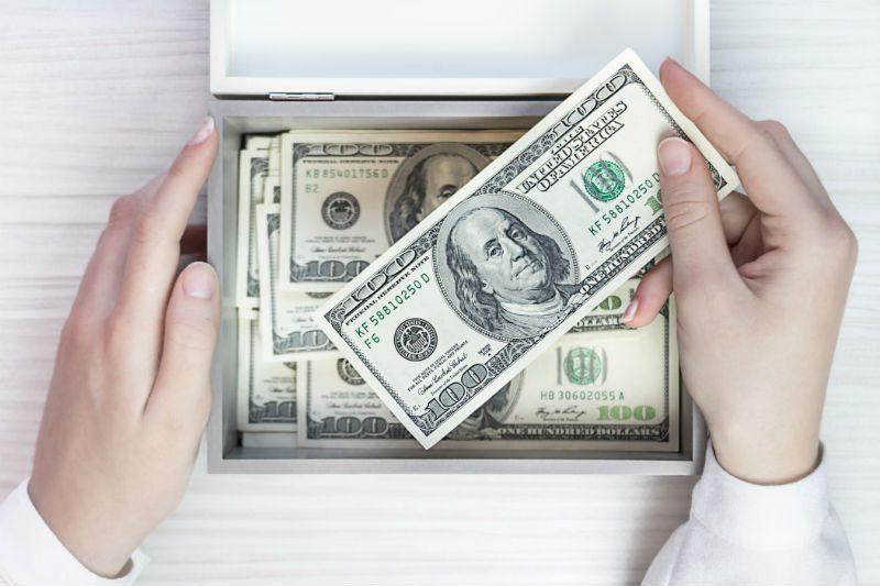 Box Full of 100 Dollar Bills With Hand Holding A Hundred Dollar Bill