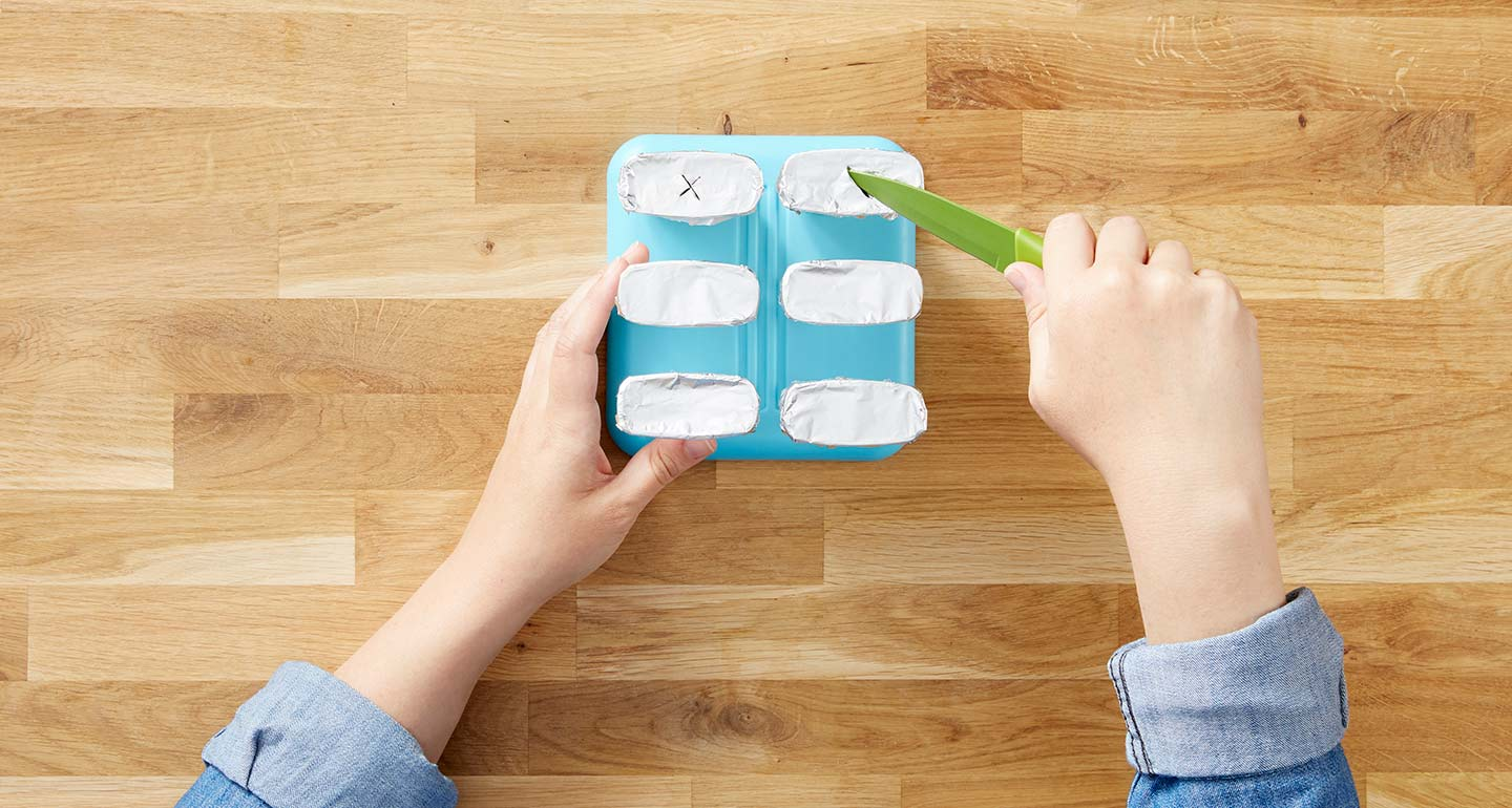 Cover each of the filled plastic molds with aluminum foil and gently cut a small X into the middle using the knife.