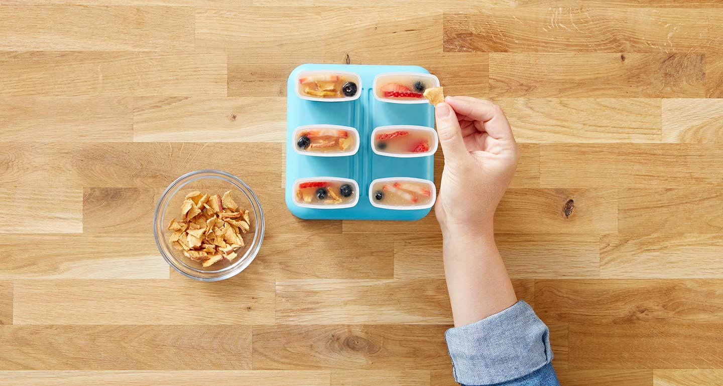 Crush the apple chips and divide them evenly among each mold.