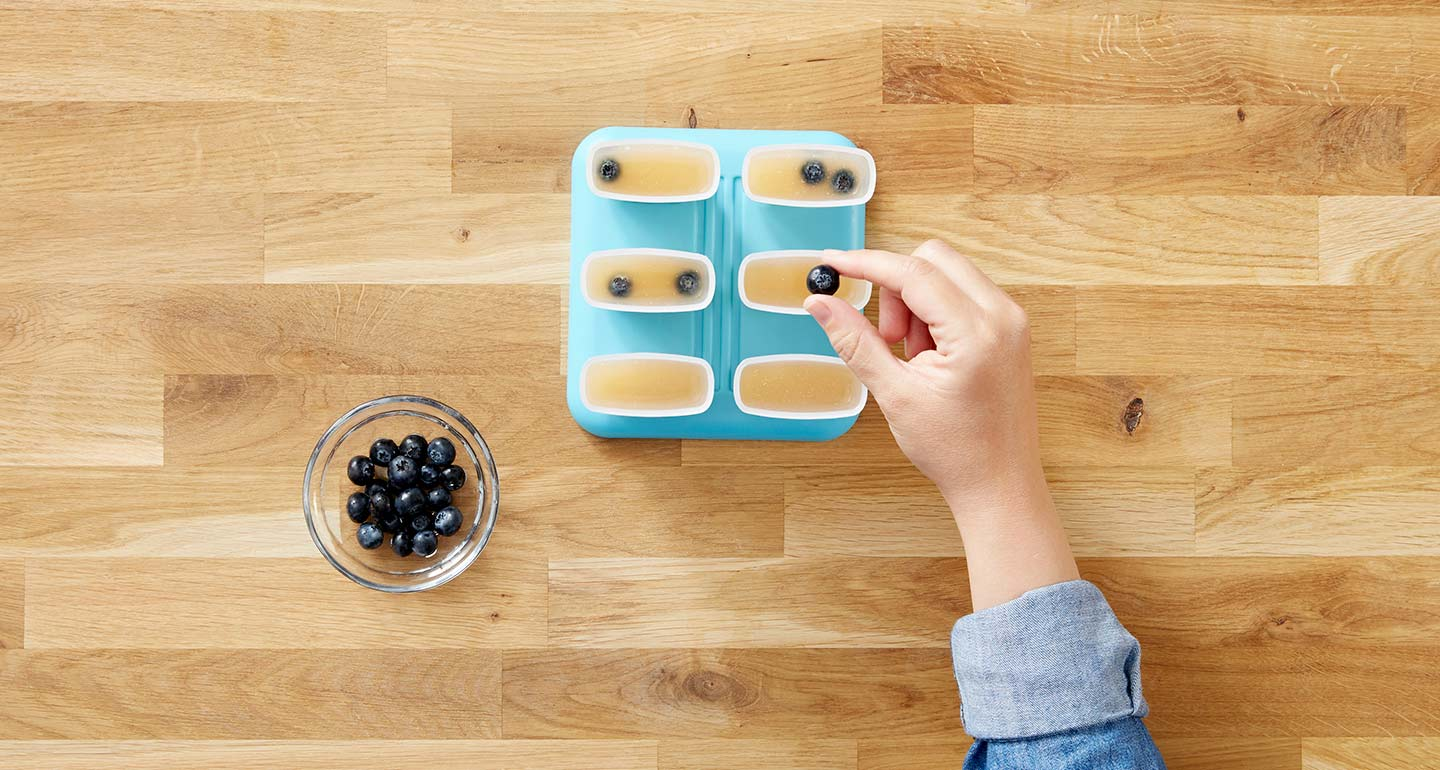 Wash the blueberries and drop 4-5 into each popsicle mold.