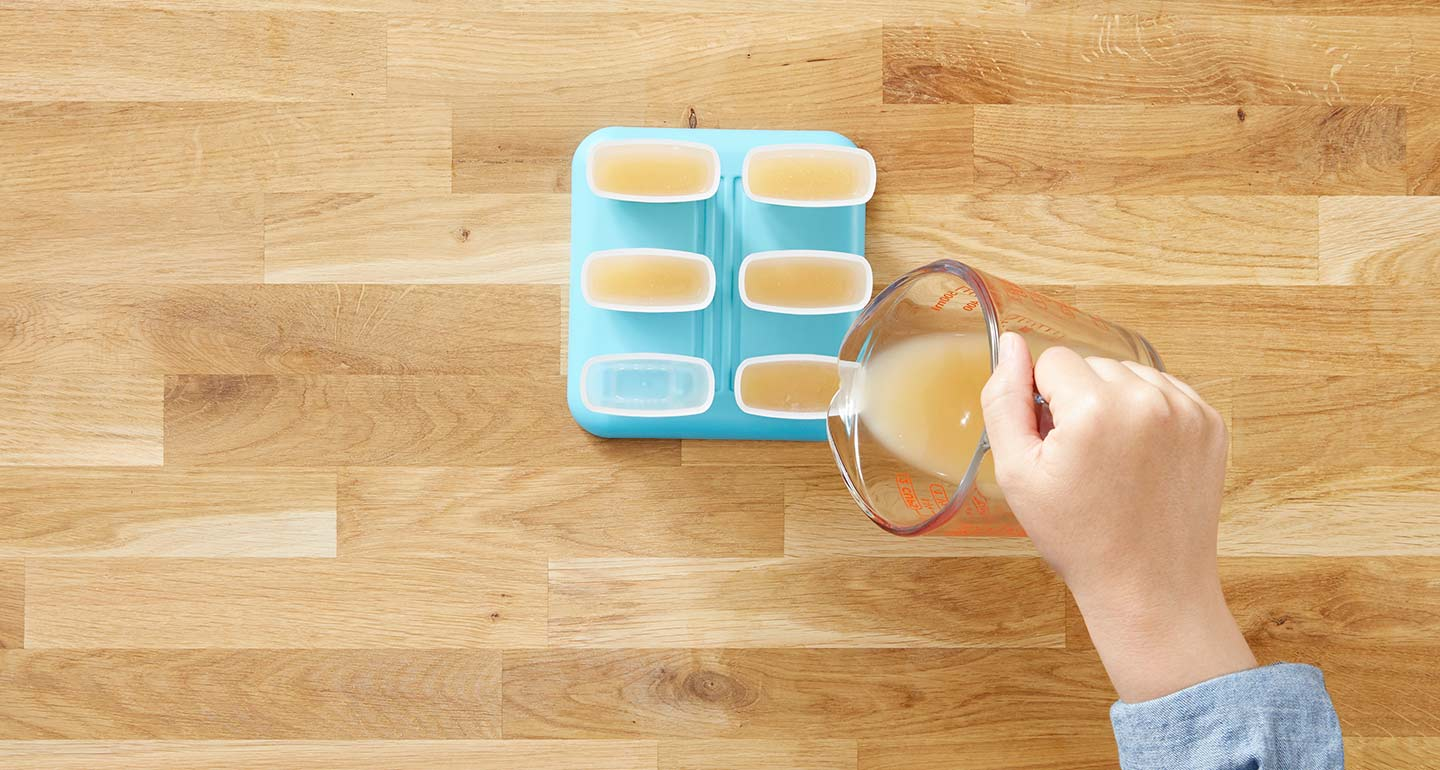 Fill each popsicle mold halfway with bone broth.
