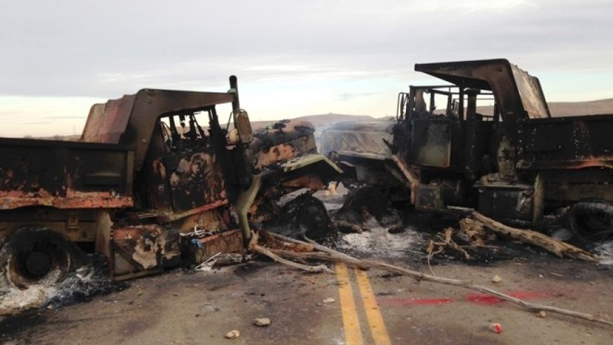 The burned hulks of heavy trucks sit on Highway 1806 near Cannon Ball, N.D., on Friday, Oct. 28, near the spot where protesters of the Dakota Access pipeline were evicted from private property a day earlier.  (AP Photo/James MacPherson)