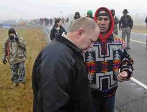 Morton County Sheriff Kyle Kirchmeier, front, listens to Brian Wesley Horinek, of Oklahoma, outside the New Camp on Pipeline Easement in North Dakota. AP photo