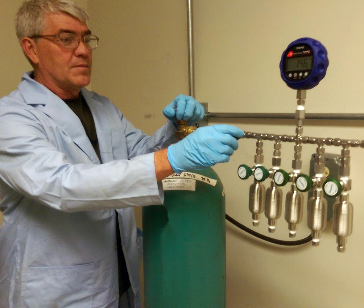 USGS Scientist Mark Dreier fills gas cylinders with samples from the natural gas standards in the Organic Geochemistry Laboratory with the USGS Energy Resources Program. Credit: Geoff Ellis, USGS