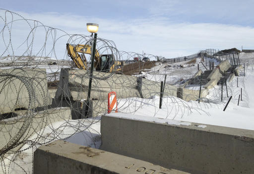 Razor wire and concrete barriers protect access to the Dakota Access pipeline drilling site . AP photo