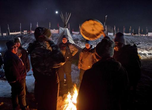 Campers gather around a fire to sing and drum traditional Native American social songs at the Oceti Sakowin camp where people have gathered to protest the Dakota Access oil pipeline in Cannon Ball, N.D., Sunday, Dec. 4, 2016. U.S. Army Corps of Engineers spokeswoman Moria Kelley said in a news release Sunday that the administration will not allow the four-state, $3.8 billion pipeline to be built under Lake Oahe, a Missouri River reservoir where construction had been on hold. (AP Photo/David Goldman)