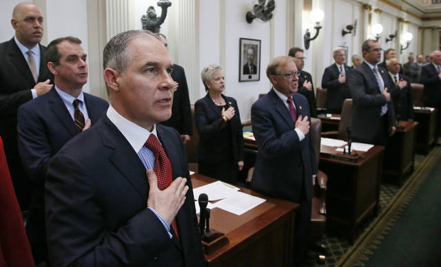 Oklahoma Attorney General Scott Pruitt, left, the U.S. Environmental Protection Agency director nominee, places his hand over his heart as he recites the Pledge of Allegiance with other state officials before the start of the State of the State speech by Gov. Mary Fallin in Oklahoma City, Monday, Feb. 6, 2017. (AP Photo/Sue Ogrocki)