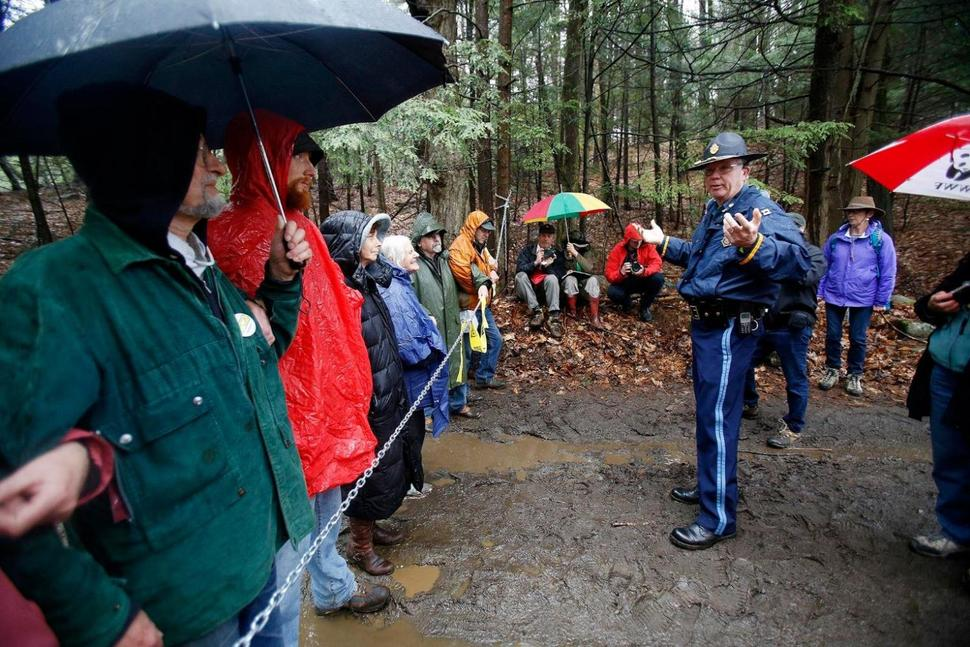 State Police Capt. James Penniman issues a notice of trespassing to protestors who have run a chain across one of the main access points for workers on the Tennessee Gas Pipeline project Tuesday, May 2, 2017, at the Otis State Forest in Sandisfield, Mass. The protestors did not leave their posts until State police officers and the Berkshire County Sheriff's Department gave them notice and arrested nine people. Stephanie Zollshan, The Berkshire Eagle via AP)