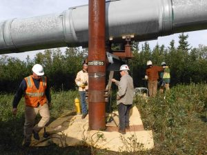 At pipeline milepost 556.5, behind Donnelly Dome, a maintenance crew works on a Vertical Support Member, which involves adjusting parts and then re-welding it in its new position.