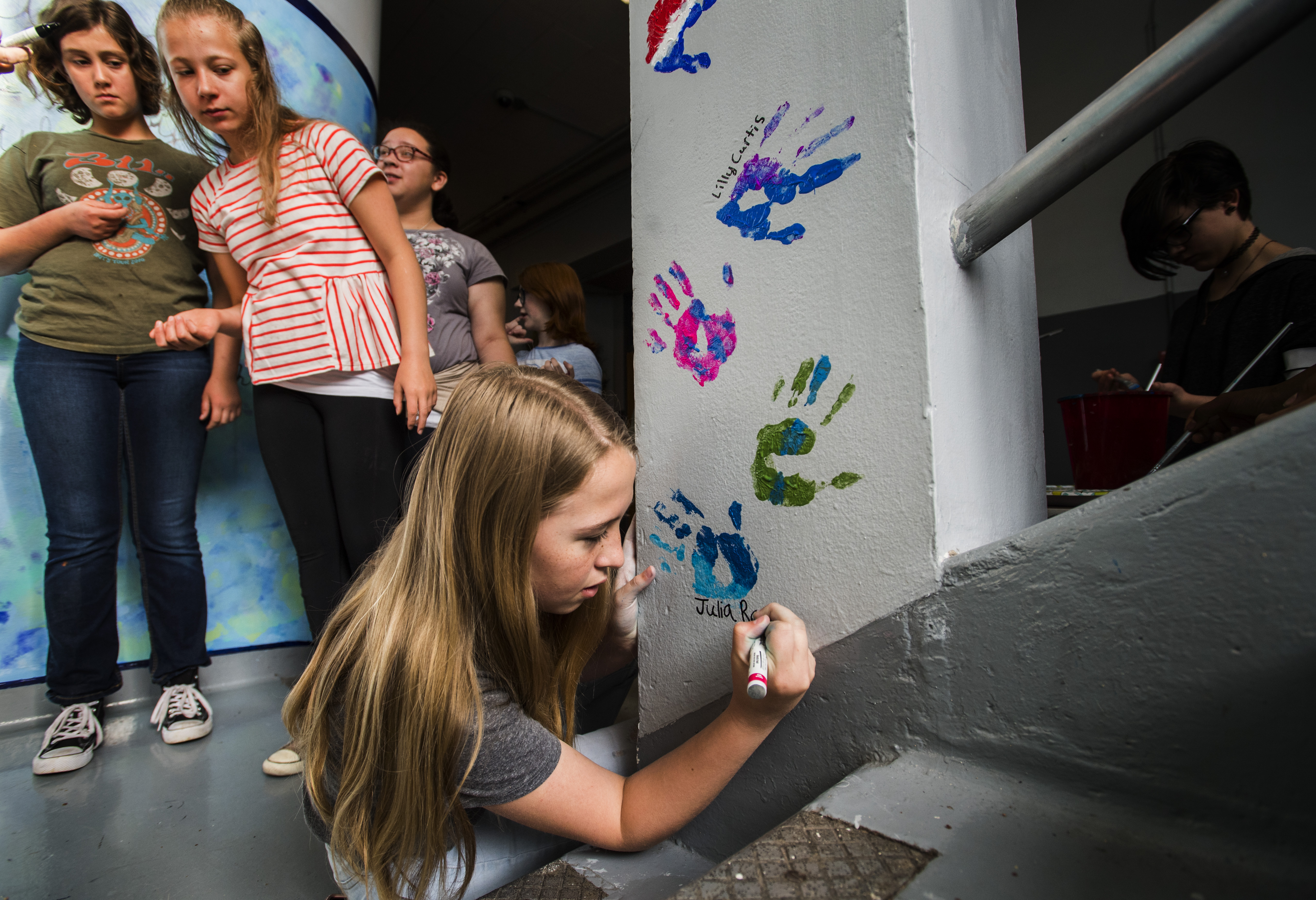 Student artist Julia Rapp signs her name below her handprint Tuesday, May 22, 2018, at North Middle School. Students in the Leadership Club spent the last month painting a mural in the lower staircase leading to school's music rooms and added their handprints and signatures as the final chapter to their work. (The Gazette, Christian Murdock)