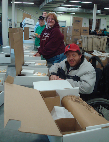 Triangle employees pack kits for Seder in a Box. From front to back: Jack, Paula, Craig and Vladimir.