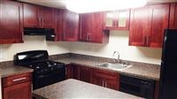 Our most recent renovation- Stunning! Toffee color cabinets, black appliances