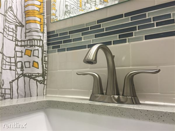 Remodeled bathroom with stone vanity top, beautiful glass mosaic and modern subway tiles