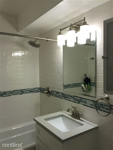 Remodeled bathroom with deep soaking tub, stone vanity top, large wash basin, extra large mirror, and contemporary lighting.