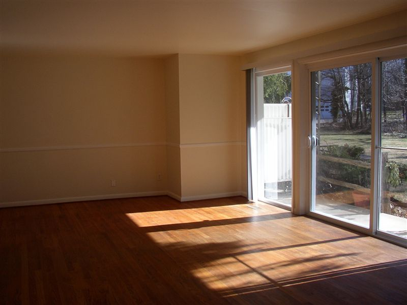 Another view of the living room from the kitchen area, showinf the sliding glass door to the patio and back yard.