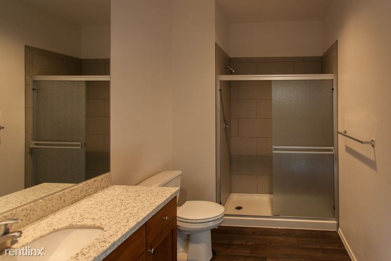Huge bathroom with large mirrors, tile shower & lots of cabinet space including a medicine cabinet.
